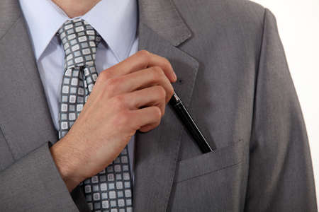 A cropped picture of a man putting a pen in his pocket. photo