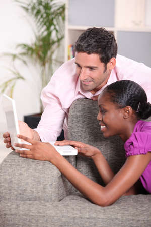Interracial couple looking at a laptop. photo
