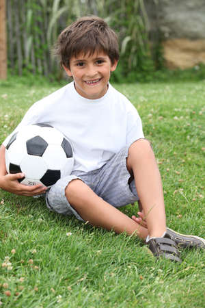 pre adolescent boy: Little boy with a football
