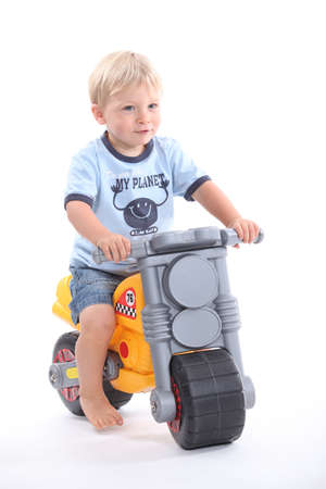 2 months: Young boy on a toy bike