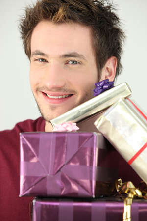 Young man with a pile of gifts photo