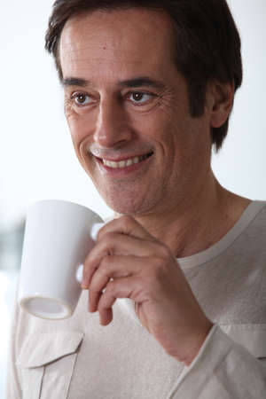 Man smiling with a cup of tea. Stock Photo - 10783125