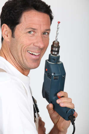 power drill: Smiling man holding an electric power drill