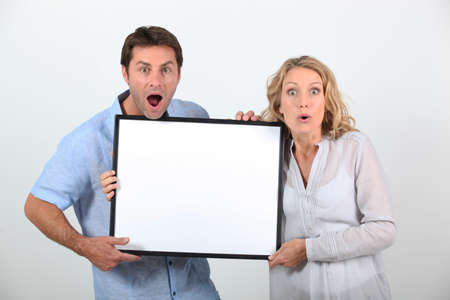 advertising board: Couple holding advertising board Stock Photo