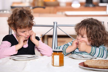 6 7 years: Grumpy children at a table with pancakes Stock Photo