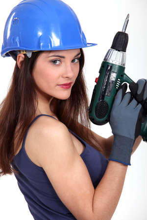 hard look: portrait of charming brunette craftswoman holding electric drill Stock Photo