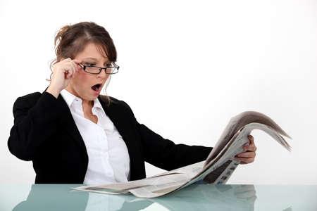 market crash: Businesswoman shocked at her newspaper Stock Photo