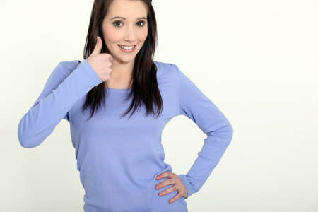 Brunette making thumbs-up gesture photo