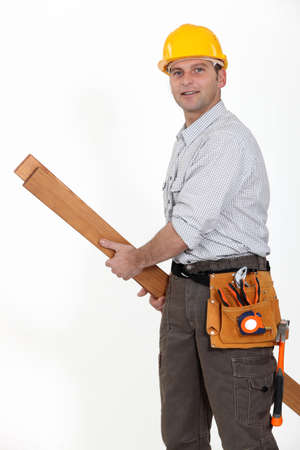 Tradesman carrying planks of wood Stock Photo - 10783539
