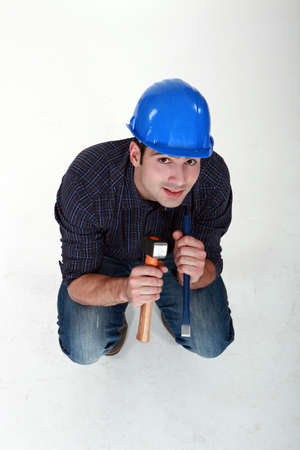 to crouch: Tradesman holding a hammer and chisel Stock Photo