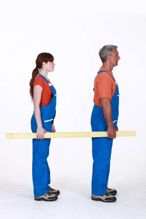 50 55: Man and woman carrying a plank of wood