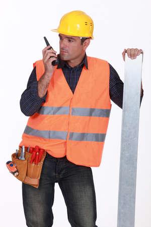 Tradesman speaking into a walkie talkie photo