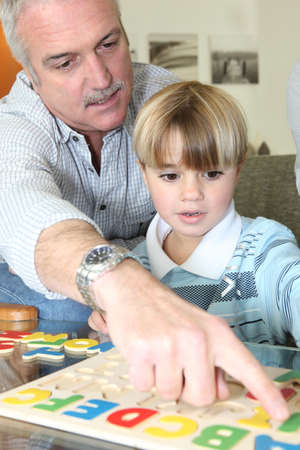 grandfather learning his grandson to read Stock Photo - 10783685