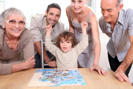 close knit: Family gathered around jigsaw puzzle Stock Photo