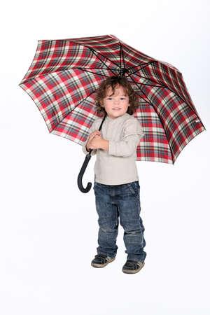 Young boy holding an umbrella Stock Photo - 10782658