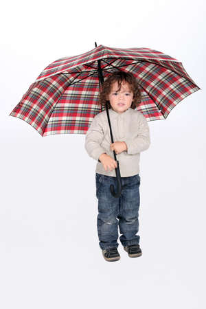 3 4 length: Young boy holding an open umbrella