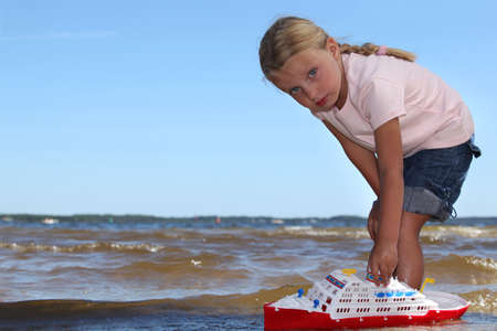 Girl playing with boat photo