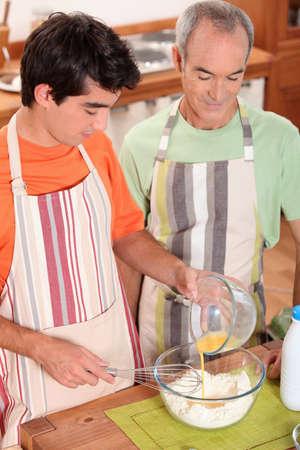 intergenerational: a teenage boy and a senior man making a cake