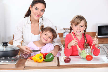 mujer hijos: Ni�os cocinando con su madre Foto de archivo