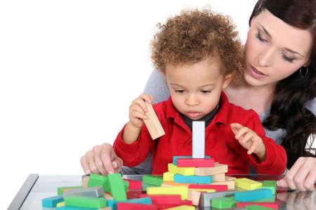 乳幼児: 女性と子供の積み木で遊ぶ