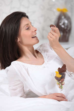 bourgeoisie: mature brunette eating Easter chocolates