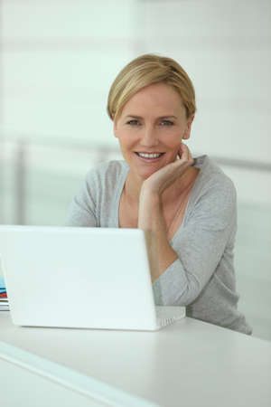 Blond woman in front of laptop computer photo