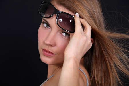 Portrait of a woman raising her sunglasses Stock Photo - 10783403