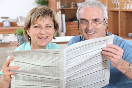Mature couple reading a newspaper together Stock Photo - 10783654