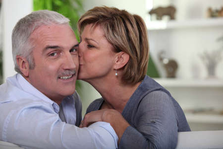 flattered: Woman kissing her husband on the cheek Stock Photo