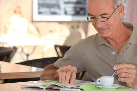 insurance policy: senior having cup of coffee