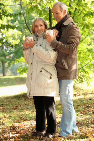 Older couple outdoors with hot drinks Stock Photo - 10783669