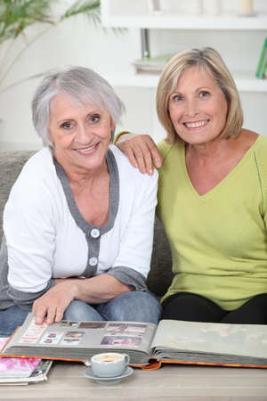aging: duo of mature women skimming through album