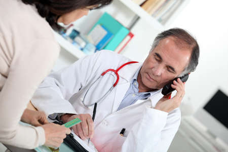 card payment: Doctor talking on the phone during a consultation Stock Photo