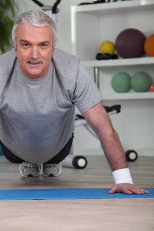 Mature man doing press ups photo