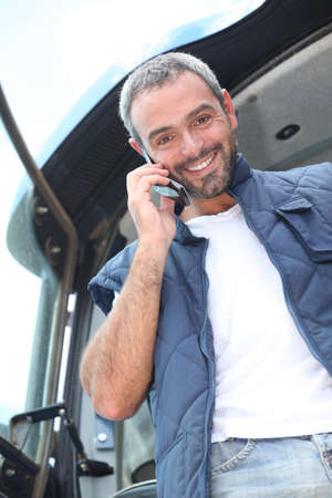 agricultural life: Farmer standing in the cab of his tractor talking on a cellphone