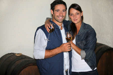 a couple drinking wine in a wine producer photo