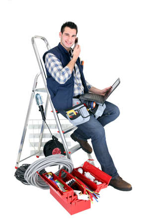 email contact: Electrician with a phone and laptop