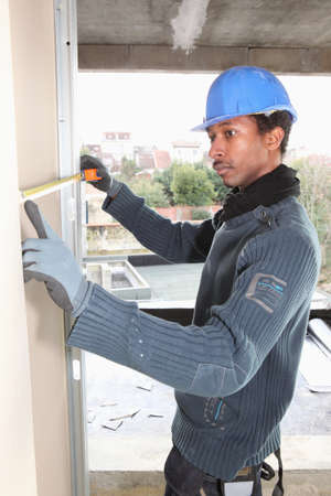 black worker with hard hat taking measurements Stock Photo - 10853486