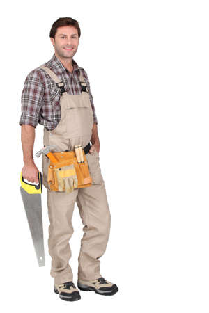 handy: Builder with saw. Stock Photo