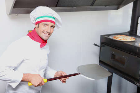 a pizza cook in front of an oven photo