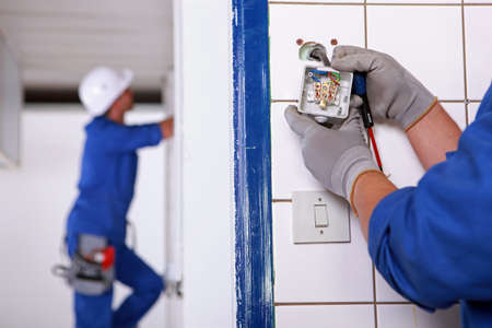 installing: Worker installing a plug Stock Photo
