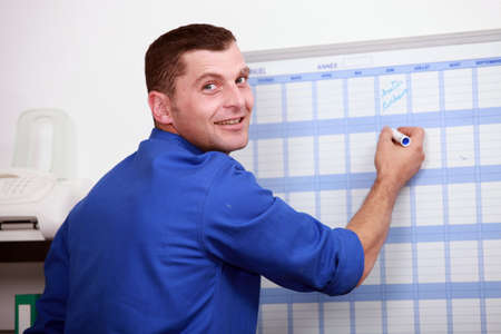 quality assurance: an employee dressed in blue jumpsuite is writing on a calendar