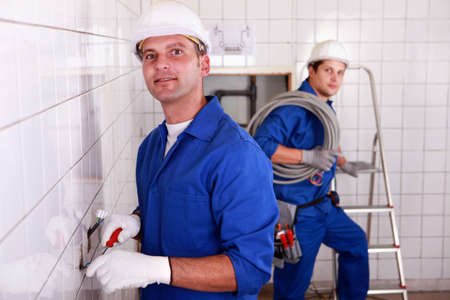 jumpsuite: two skilled tradesman in blue jumpsuites working in a empty room Stock Photo