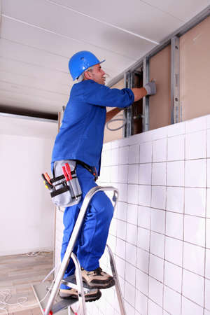 panelling: Construction worker panelling wall Stock Photo
