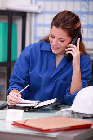 schedule appointment: Woman wearing blue overalls speaking on telephone