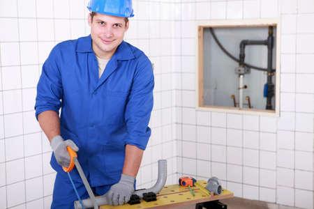 Plumber cutting plastic pipe photo