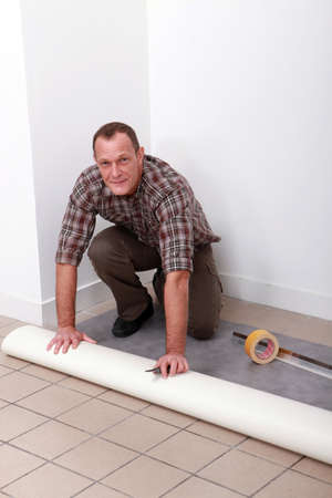 tile flooring: Man laying pvc flooring