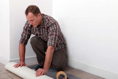 handyman laying linoleum photo