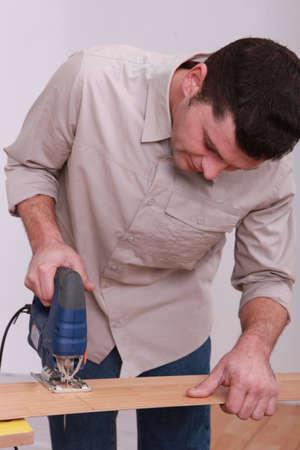 Man using an electric jigsaw photo