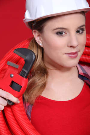 fix jaw: Female plumber in red with a red pipe and wrench